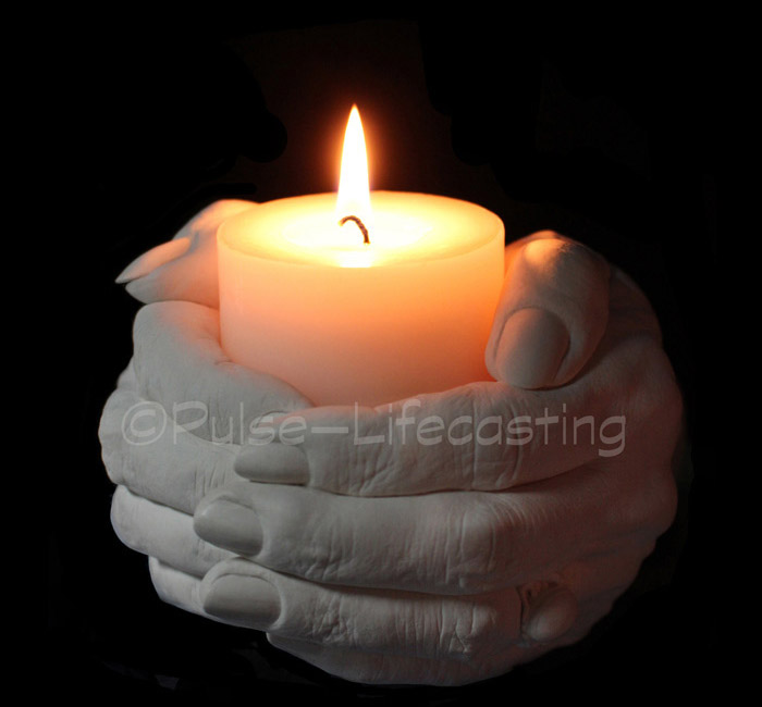 Cast of hands holding a memorial candle